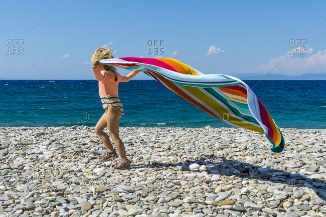 Little girl playing with towel on rocky beach