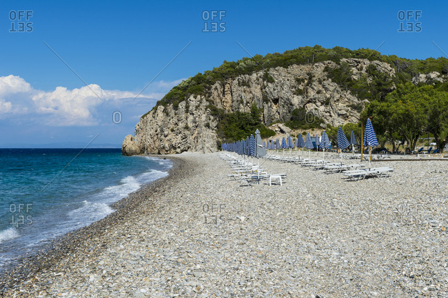 Greece- North Aegean- Rows of beach umbrellas and empty deck chairs on Tsambou beach in summer