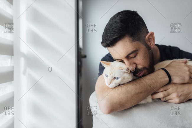 Mid adult man embracing cat in arms while sitting at home