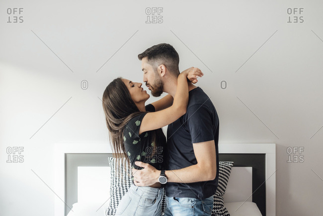 Romantic couple embracing each other while kneeling on bed at home