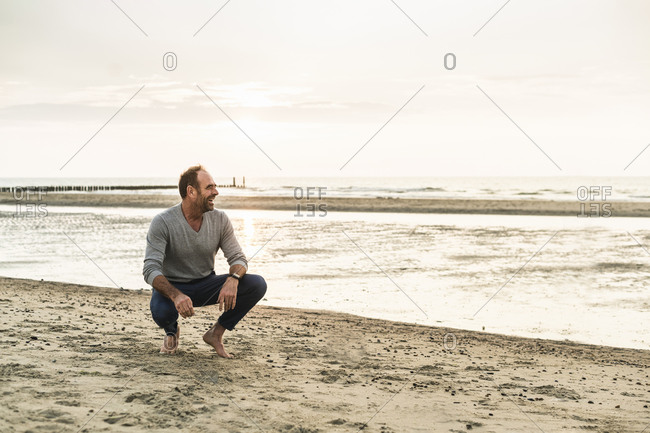 Mature man laughing while crouching at beach against sky during sunset