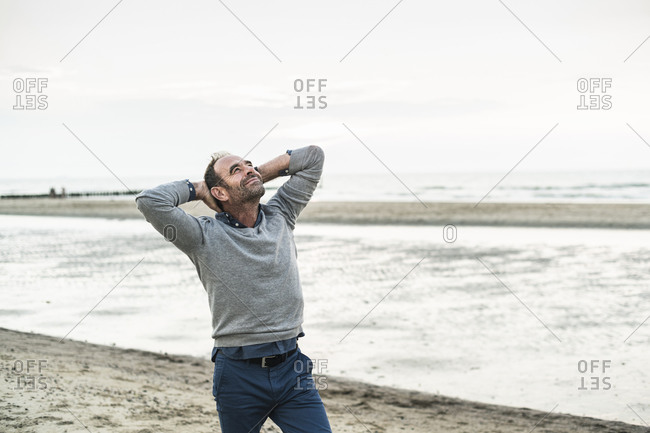 Carefree mature man with hands behind head standing against sea
