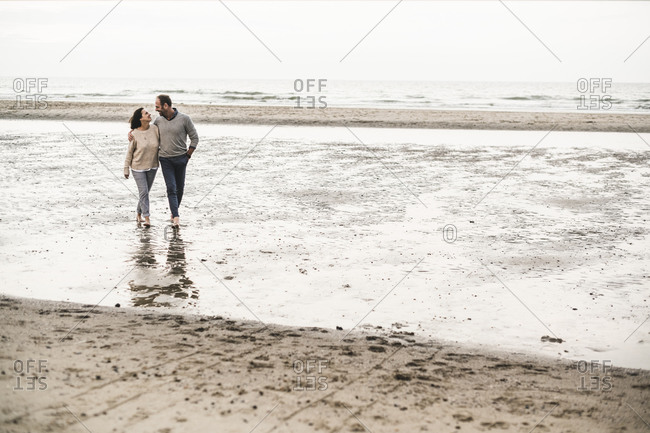 Romantic couple walking on beach against sky during sunset