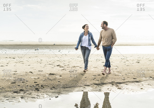 Happy couple holding hands while enjoying weekend at beach during sunset