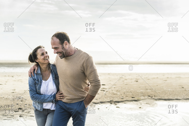 Cheerful mature couple embracing while standing against sea during weekend