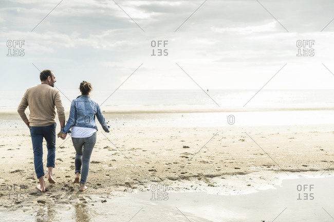 Couple holding hands while walking at beach against cloudy sky during sunset