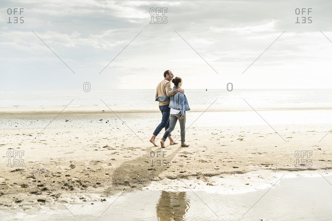 Couple with arms around walking at beach against cloudy sky during sunset