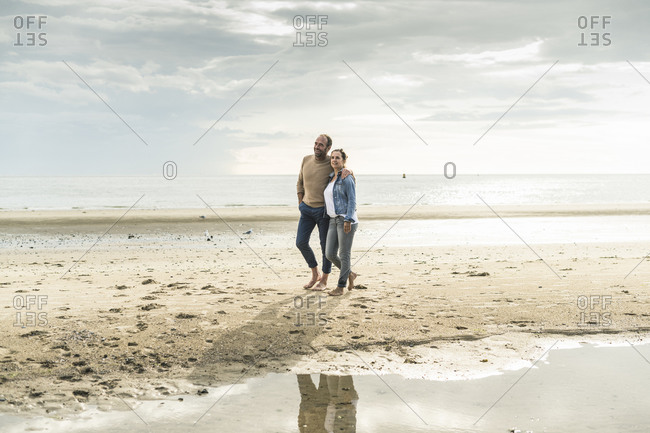 Mature couple spending leisure time at beach during sunset