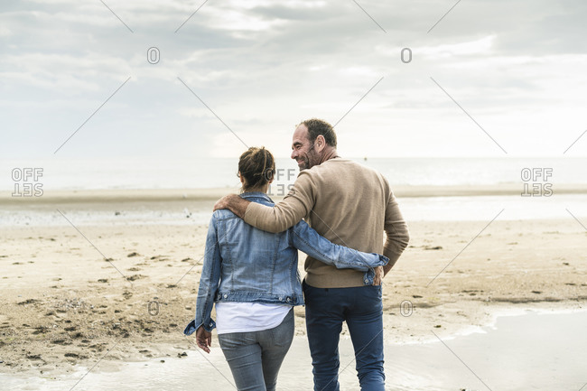 Couple with arms around spending leisure time at beach during weekend