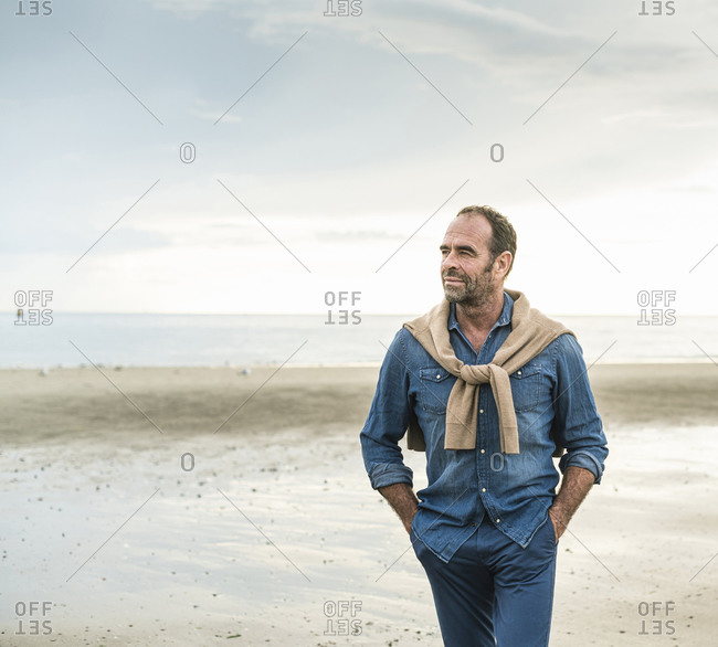 Thoughtful mature man walking at beach against cloudy sky
