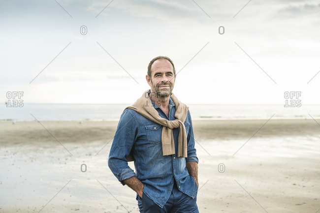 Mature man with hands in pockets standing against sea during weekend at sunset