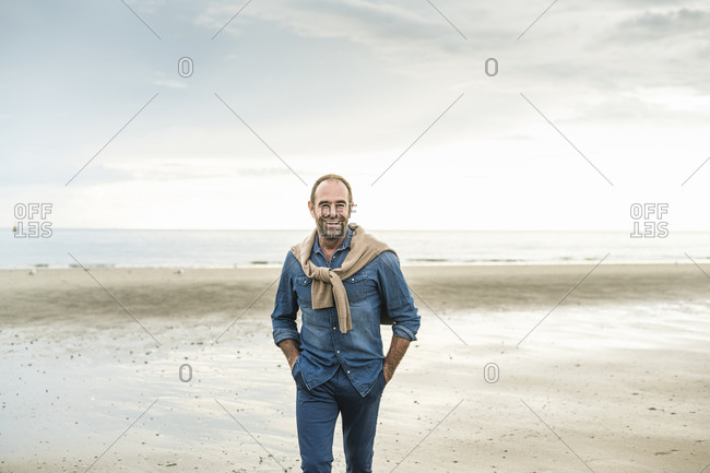Cheerful mature man with hands in pockets walking against sea during sunset