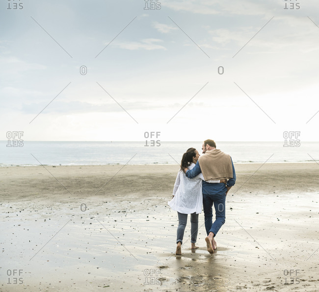 Mature couple with arms around enjoying weekend at beach against cloudy sky