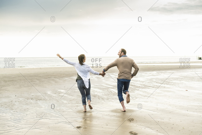 Cheerful couple holding hands while running at beach during sunset