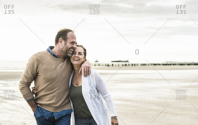 Cheerful man embracing woman while standing against sea during sunset