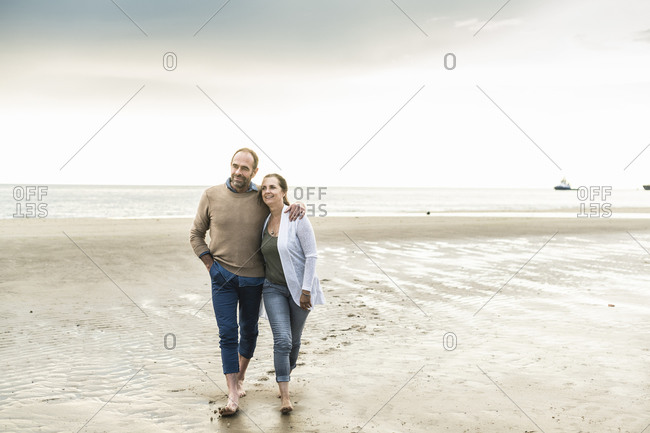 Mature couple spending weekend at beach against sky during sunset