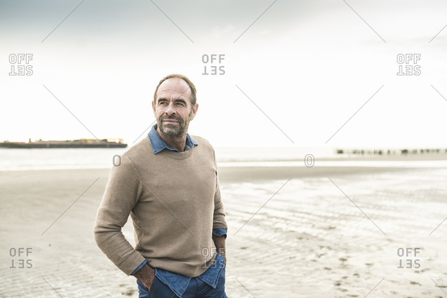 Mature man contemplating while standing at beach against sky