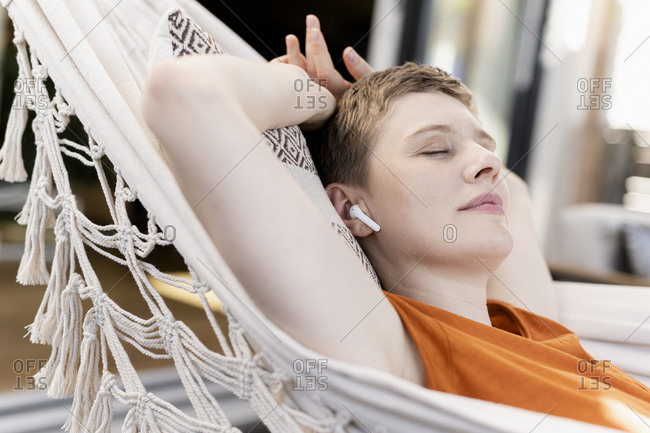 Close-up of woman listening music through wireless headphones while napping on hammock