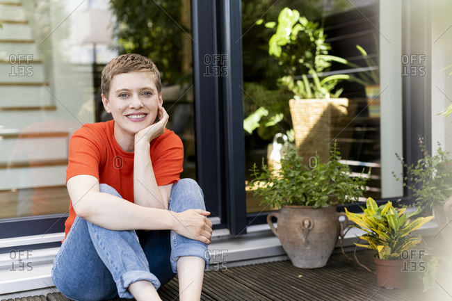 Smiling beautiful woman with hand on chin sitting against house in yard