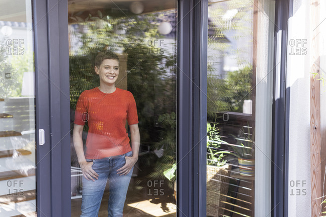 Thoughtful woman looking through window while standing at home seen through glass