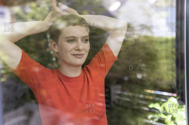 Close-up of thoughtful woman with arms raised standing at home seen through window