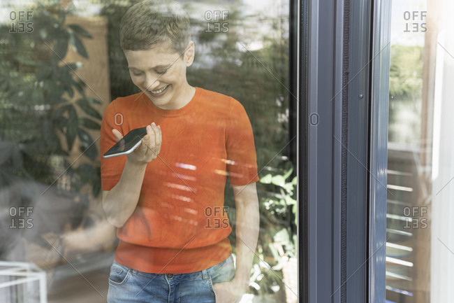 Smiling woman talking over mobile phone while standing by window at home seen through glass