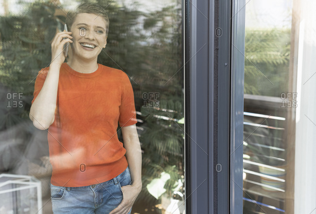 Cheerful woman talking over smart phone at home seen through window