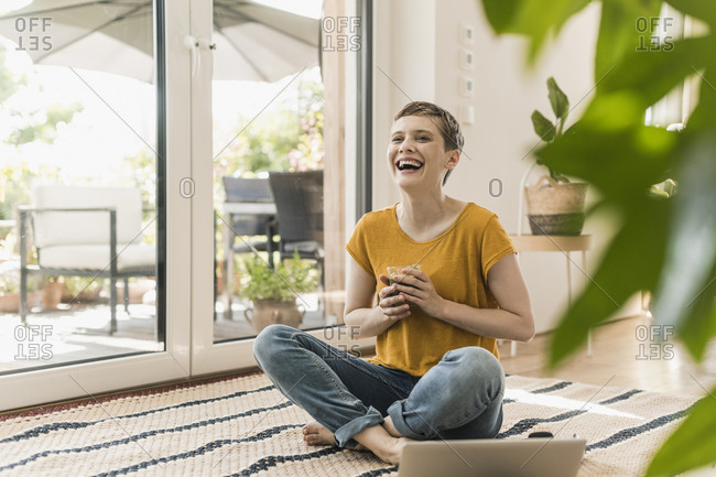 Cheerful woman holding drink laughing while sitting with laptop on carpet at home