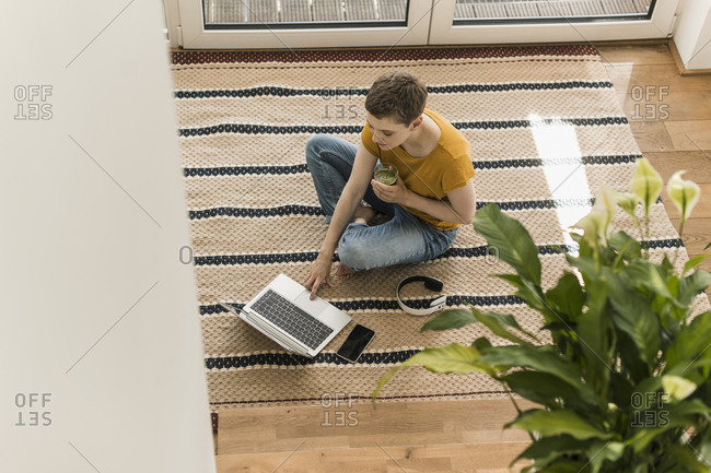 Woman with short hair holding drink while using laptop on carpet at home