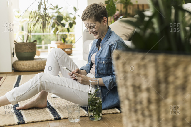Smiling mid adult woman with short hair using smart phone while sitting on carpet at home
