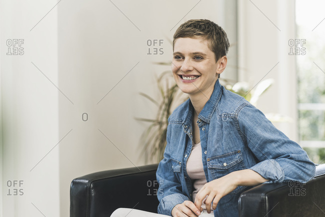 Smiling woman with short hair looking away while sitting on armchair at home