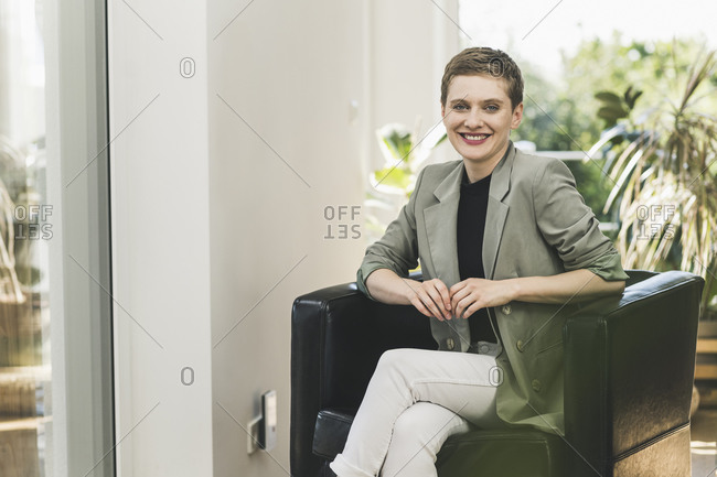 Smiling businesswoman with short hair sitting on armchair at home