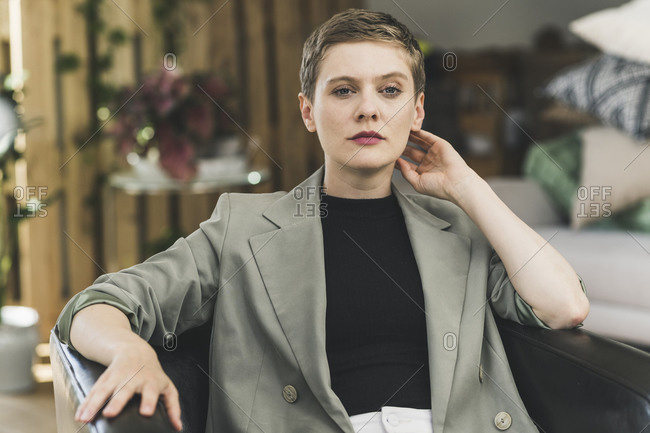 Confident businesswoman wearing blazer sitting on armchair at home