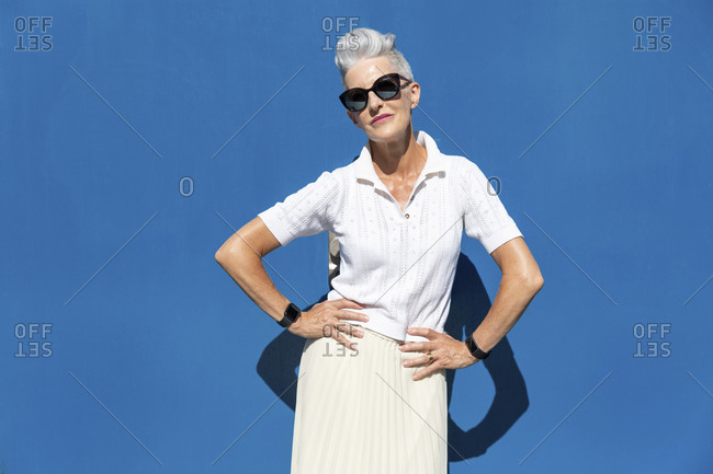 Senior woman standing with hand on hip against blue wall during sunny day