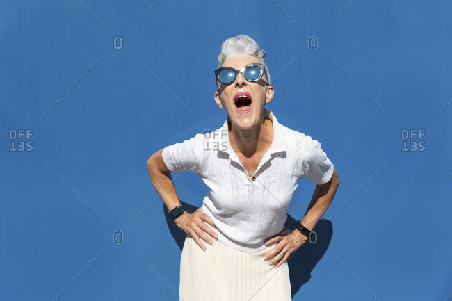 Woman with mouth open and hand on hip standing against blue wall during sunny day