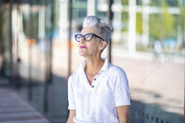 Smiling senior woman looking away while standing against glass window