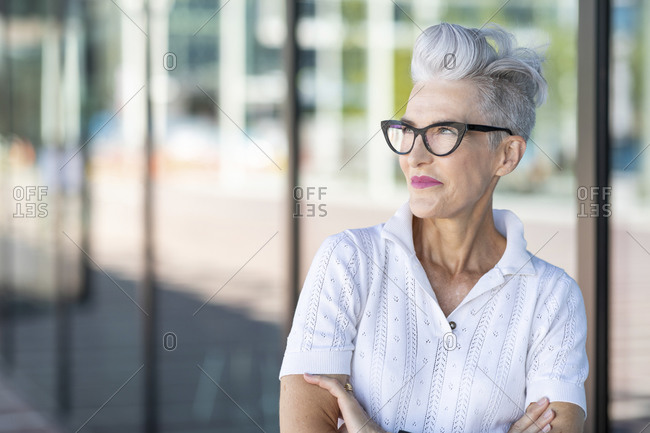 Smiling senior woman with arms crossed looking away while standing against glass window