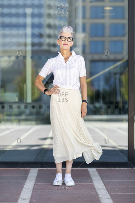 Senior woman standing with hand on hip against glass window in city