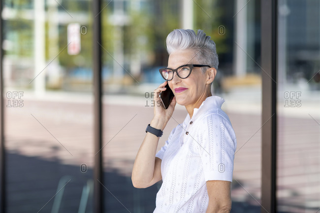 Smiling woman talking on smart phone against glass window