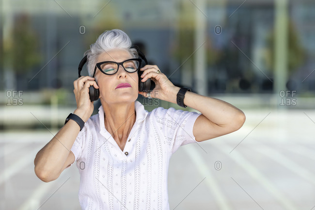 Senior woman listening to music through headphones against glass window