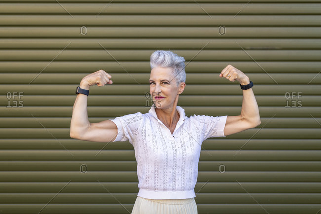 Senior woman flexing muscles while standing against shutter