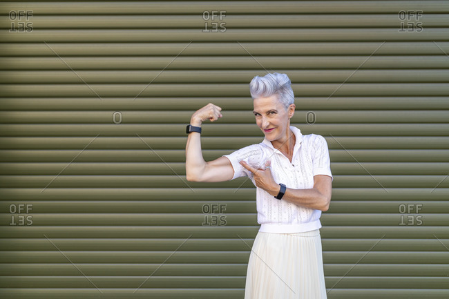 Active senior woman pointing at bicep while flexing muscles while standing against shutter