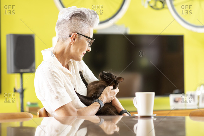 Senior woman playing with cat while sitting at home