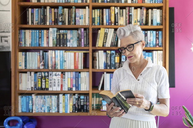 Active senior woman reading book while standing against bookshelf at home
