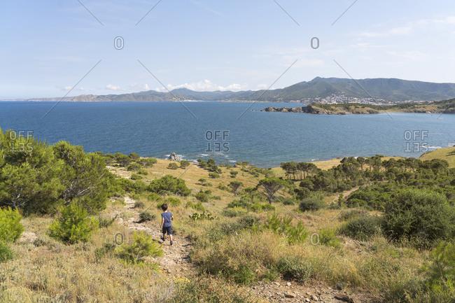 Little boy hiking along sunny coast of Costa Brava