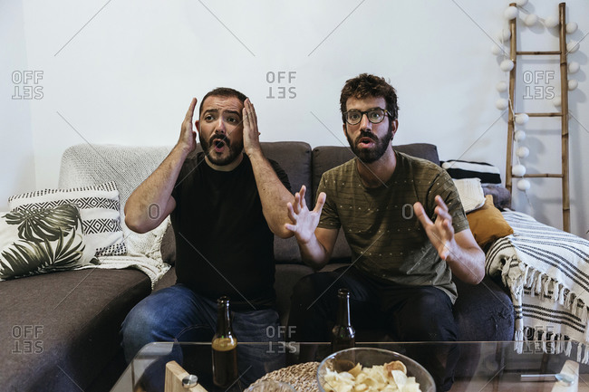 Stressed male friends watching sports while sitting on sofa at home