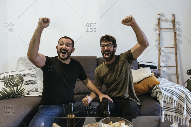 Cheerful male spectators screaming while watching sports in living room