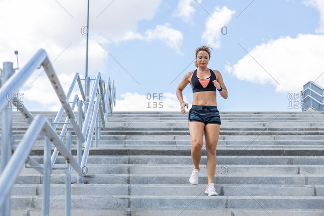 Woman running down stairs outside, front view