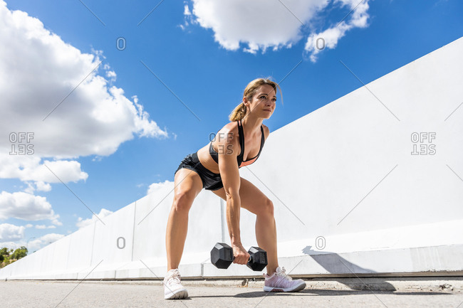 Mature woman training with her dumbbell outdoors, arm down, side view