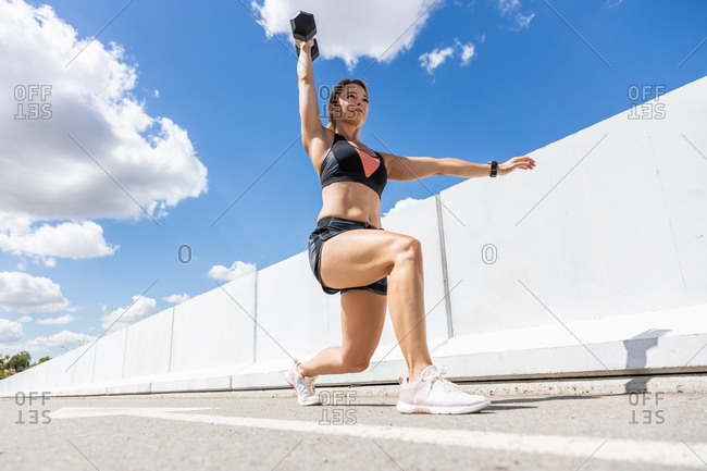Mature woman training with her dumbbell outdoors, arm down and bent knee, side view